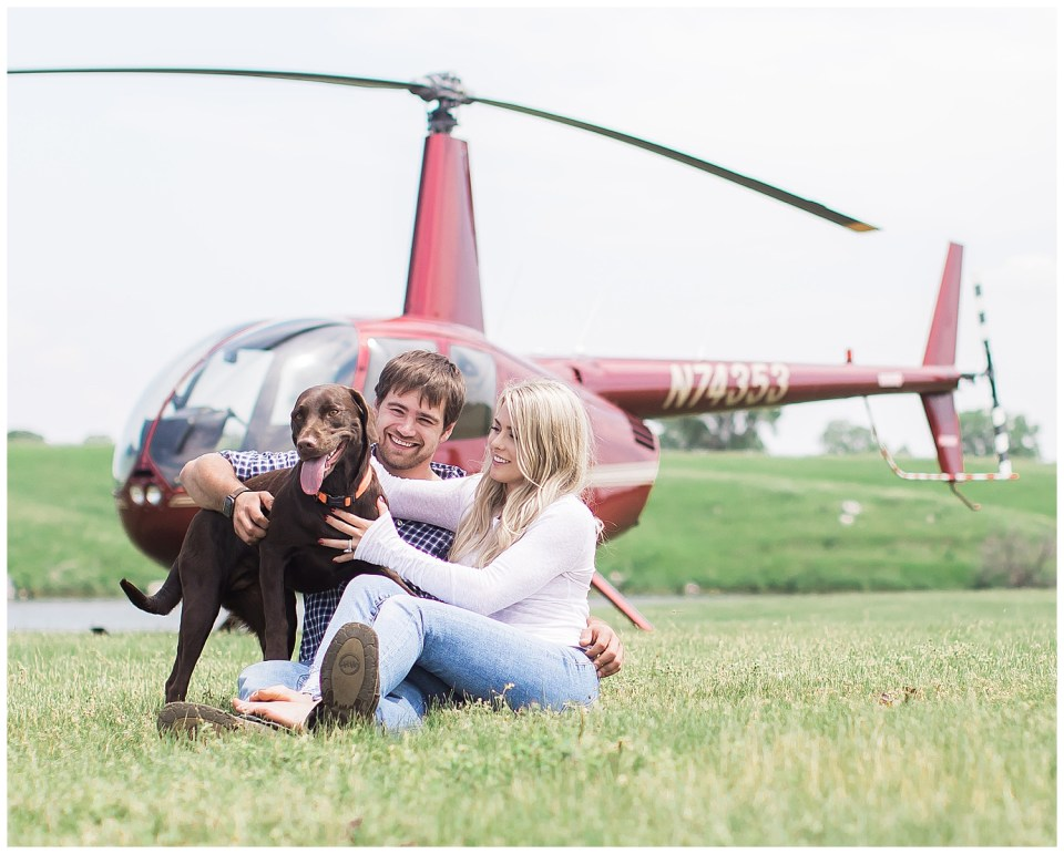 Couple posing with their dog in front of helicopter during their engagement session with Solis Photography