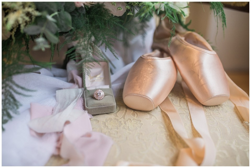 Detail shot of a ring box holding a ring and ballerina shoes on top fo a chair during a fine art wedding photoshoot in South Dakota