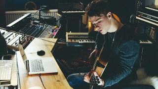 ギターを弾く青年の画像