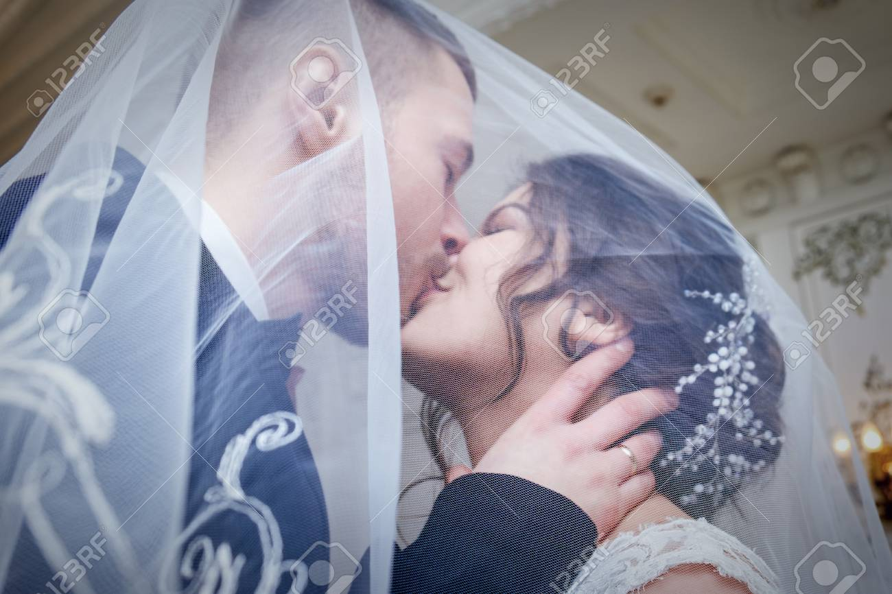 95967100-under-the-veil-the-bridegroom-kisses-the-bride-with-closed-eyes-the-faces-of-young-people-are-slight.jpg