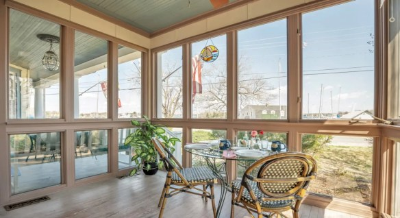 Large enclosed sunroom with glass table and two wicker chairs and a view to the outside