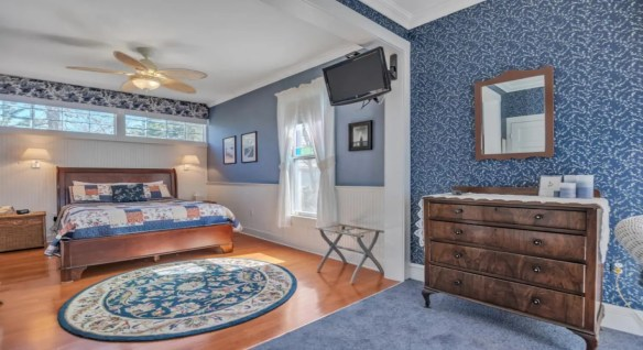 Bedroom with blue-gray walls, white wainscoting, hardwood flooring, dark wooden furniture, ceiling fan, and TV mounted on the wall