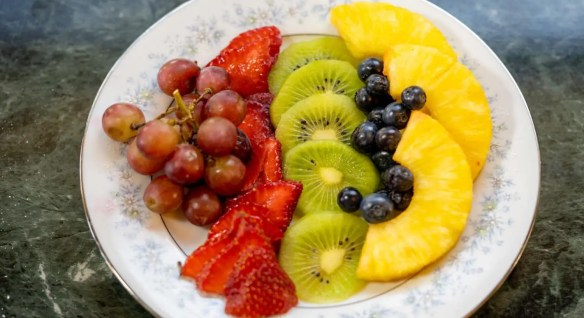 Close up view of sliced strawberries, kiwi, and pineapple, grapes and blueberries