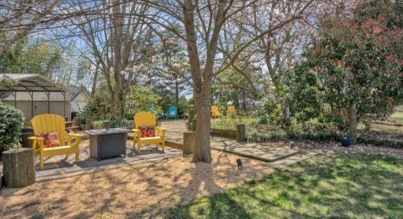 Two bright yellow adirondack chairs each with a floral patterned pillow surrounded by green shrubs and trees