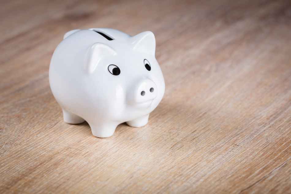 white piggy bank on brown wooden surface