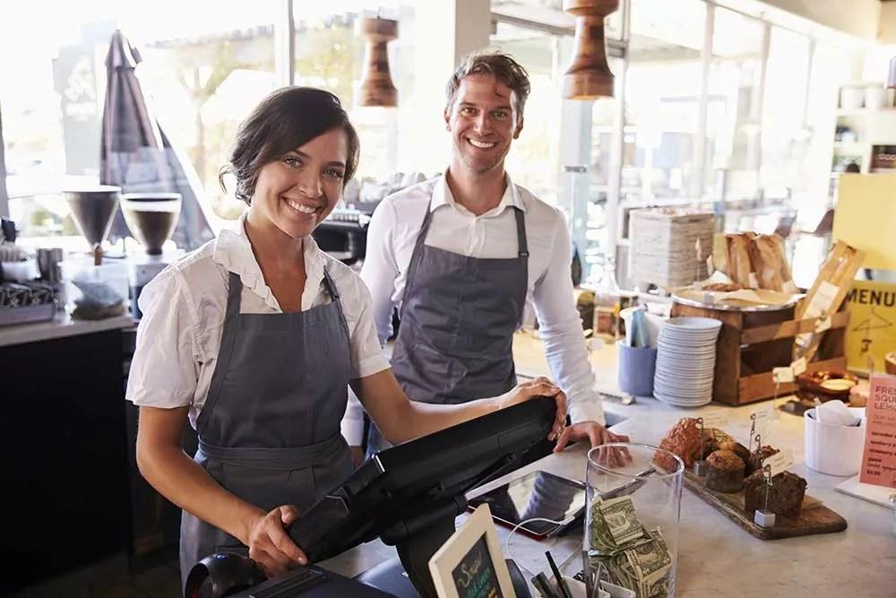 vendeurs qui encaisse sur une caisse tactile dans un magasin