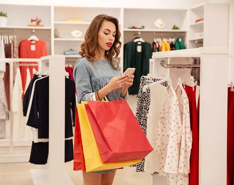 une cliente dans un magasin recoit un sms promotionnel
