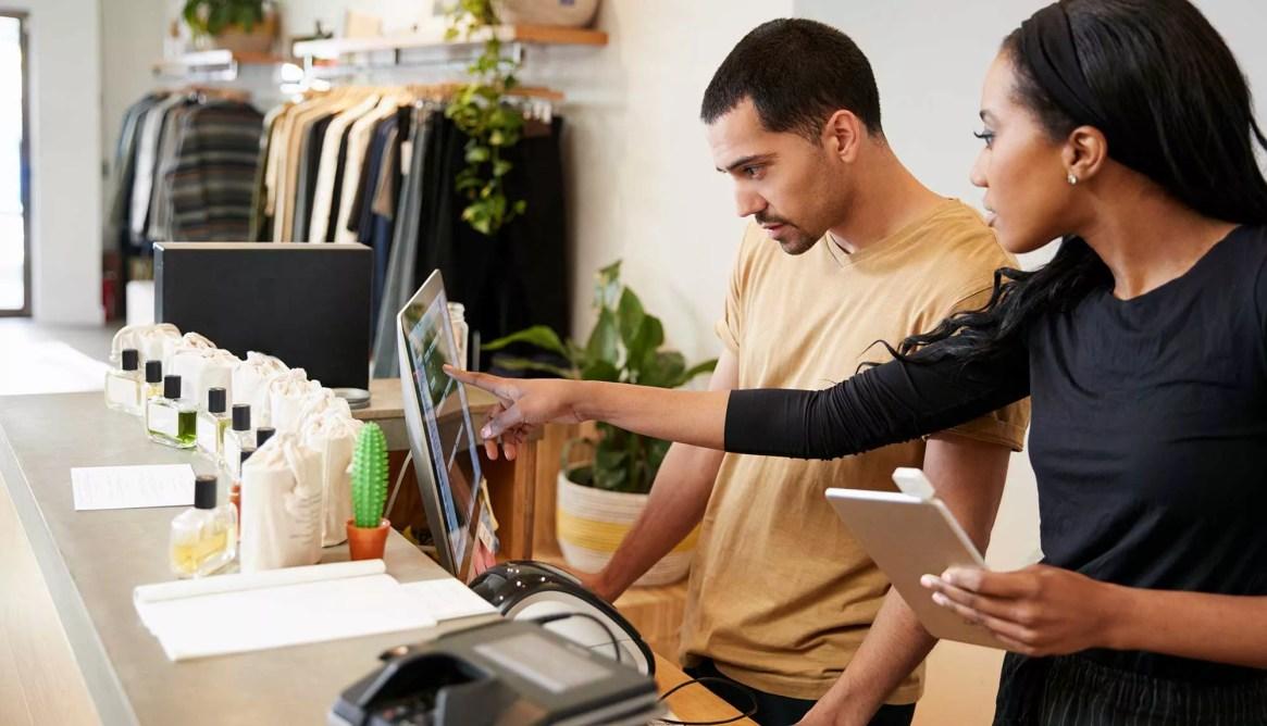 Un commercant regarde son logiciel de caisse dans son magasin