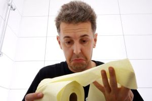 A depressed man with IBS symptoms looking at toilet paper