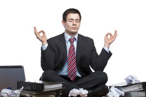 Business man meditating to reduce stress and IBS.