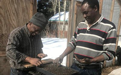Muhidin and Hassan seeding trays at Liberation Farms