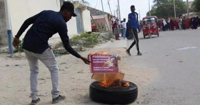 A man burns a poster of Somali President Mohamed Abdullahi Mohamed in Mogadishu in December 2020