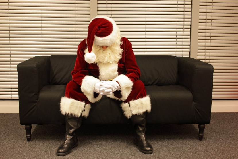 Sad and depressed Santa Claus waiting for christmas job sitting