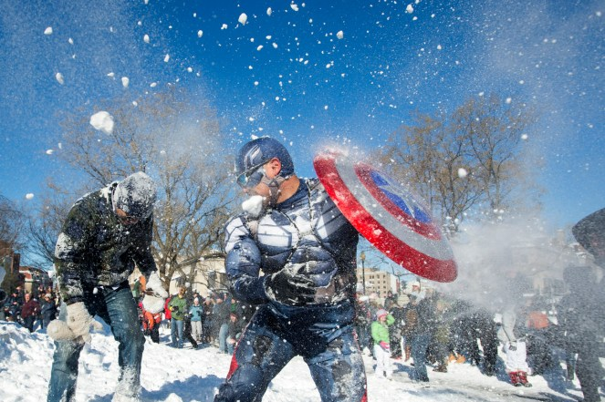 epa05123218 Jeff Dacanay (C), while dressed as Captain America, is pelted with snow during a snowball fight following a blizzard, at Dupont Circle in Washington, DC, USA, 24 January 2016. The nation's capital is beginning to recover from a major blizzard, Winter Storm Jonas, that dumped near-record amounts of snow in Washington DC. EPA/MICHAEL REYNOLDS