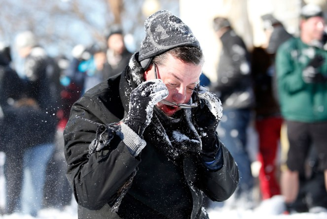 A man reacts after being hit in the face with a snowball during an organized snowball fight at Dupont Circle Sunday, Jan. 24, 2016 in Washington. People throw snow during an organized snowball fight at Dupont Circle Sunday, Jan. 24, 2016 in Washington. Millions of Americans were preparing to dig themselves out Sunday after a mammoth blizzard with hurricane-force winds and record-setting snowfall brought much of the East Coast to an icy standstill.(AP Photo/Alex Brandon)