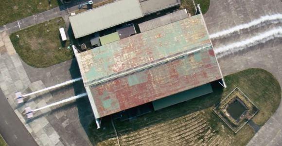 Dois aviões atravessam um hangar em rasante de tirar o fôlego
