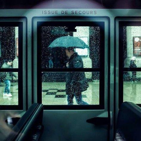 Homem de guarda-chuva através da janela do metrô