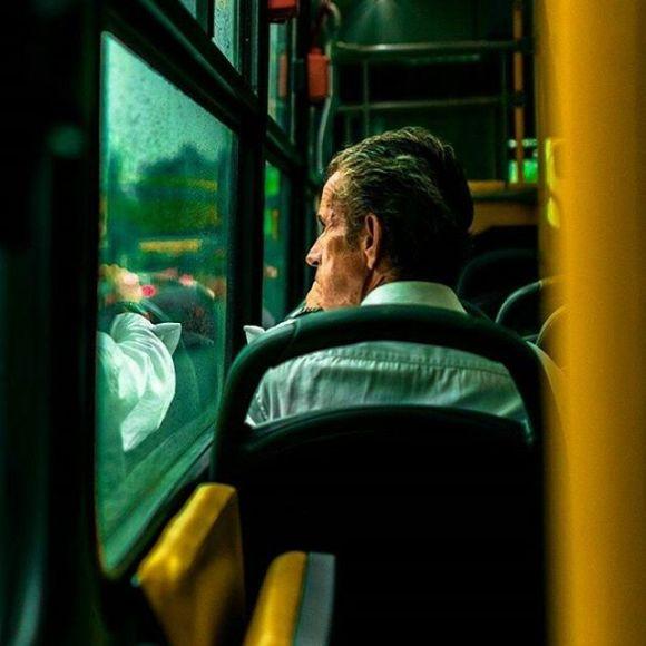 Homem olhando através da janela do ônibus