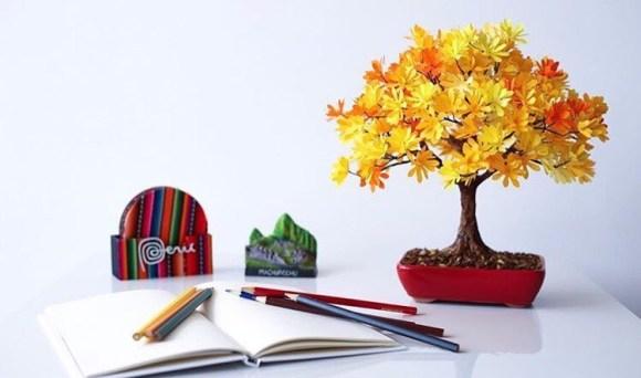 Bonsai amarelo em cima da mesa com caderno e canetas