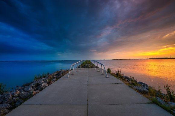 Do lado esquerdo, céu e água azuis, no centro um mirante e do lado direito por do sol