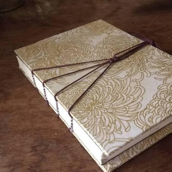 Caderno A6, 80 páginas, com fios para fechar e tecido com fios de ouro.