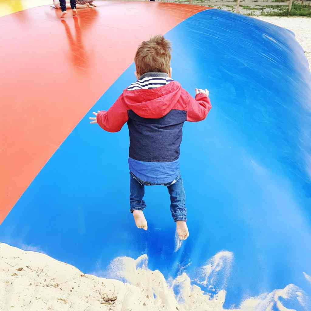 boy in mid-air jumping on an inflatable 'pillow'