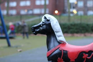 A horse toy in a park.