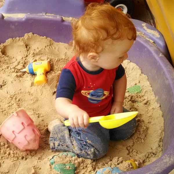 baby playing in sandbox with jeans on