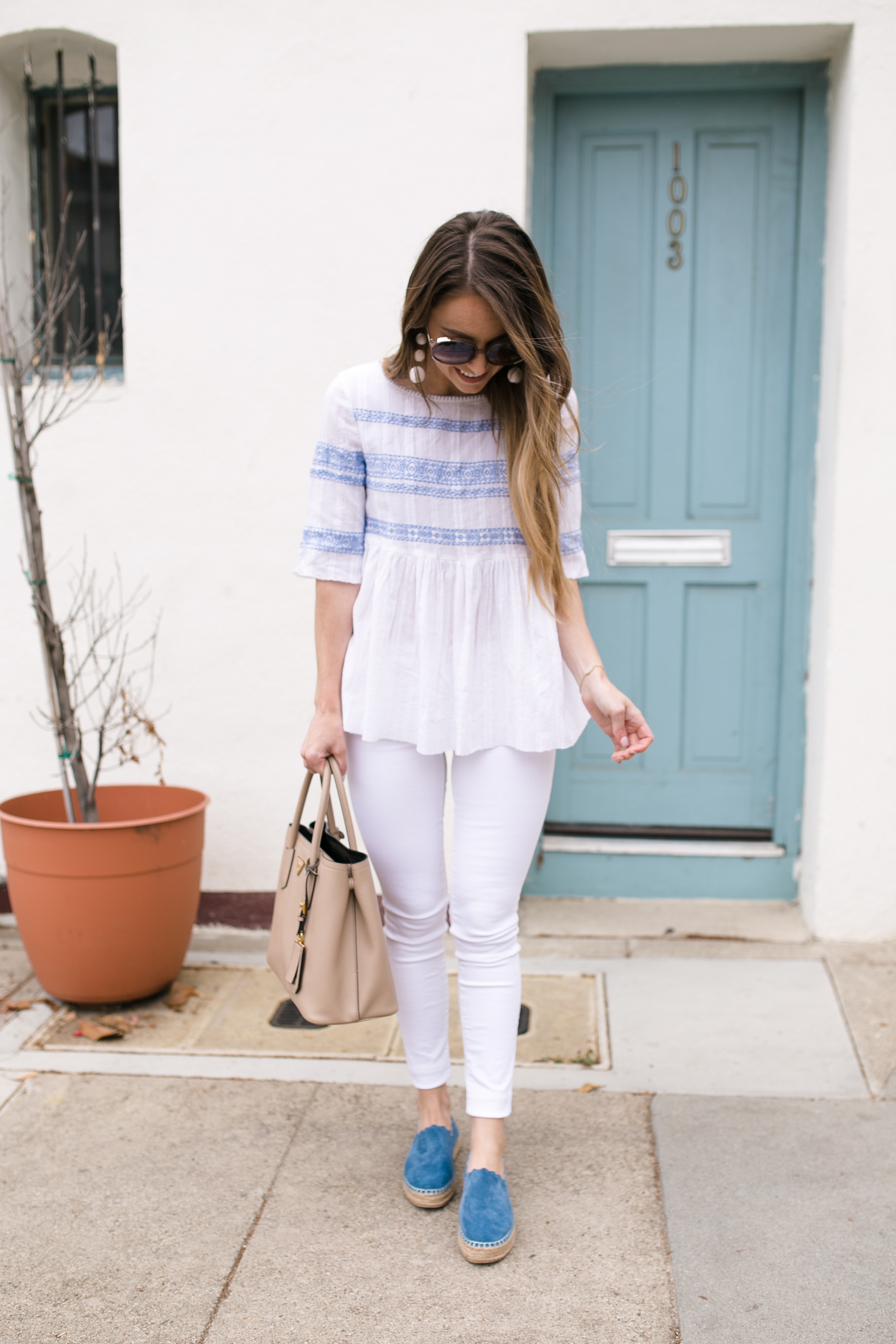 Style blogger Daryl-Ann Denner wearing an embroidered blue and white top with white jeans and chloe espadrille dupes
