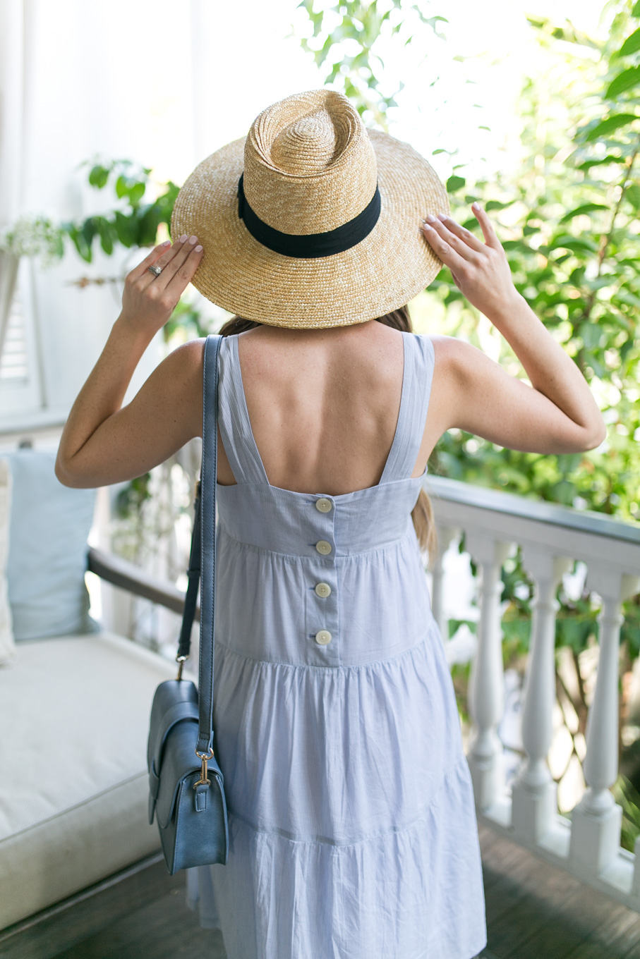 Style blogger, Daryl-Ann Denner, wears Madewell Marcelline Tiered Stripe Midi Dress and Brixton Joanna Straw hat from Nordstrom in Charleston
