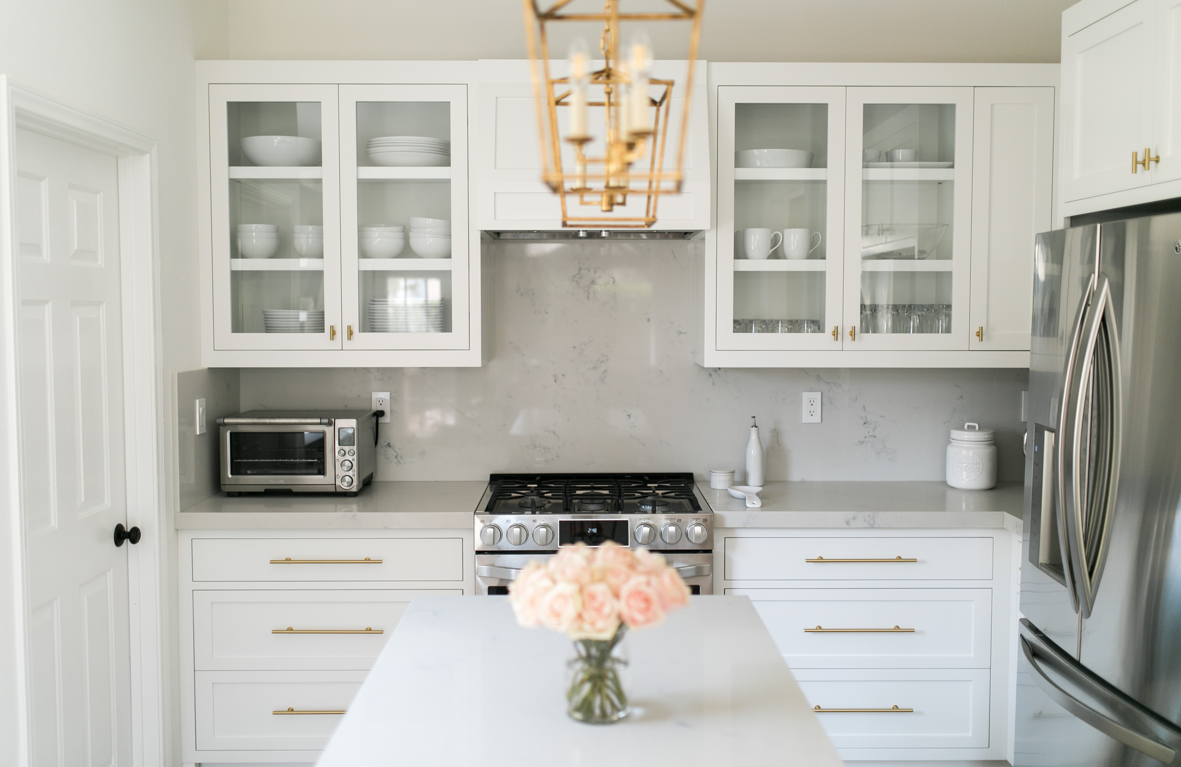 daryl-ann denner reveals white marble kitchen with gold lanterns and gold hardware and white dishes