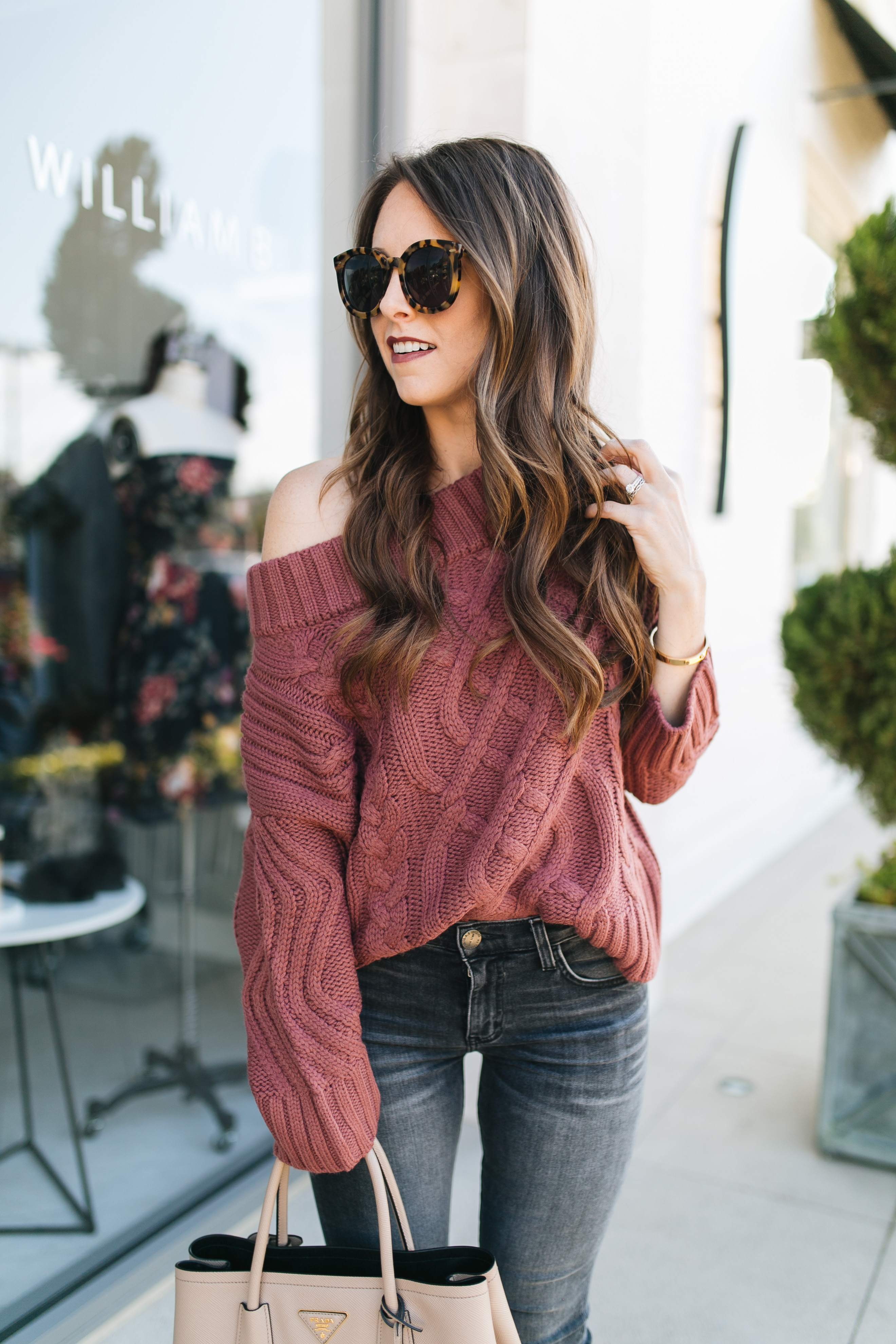 Fashion blogger daryl-ann denner styles a fall outfit with off-the-shoulder sweater and gray jeans