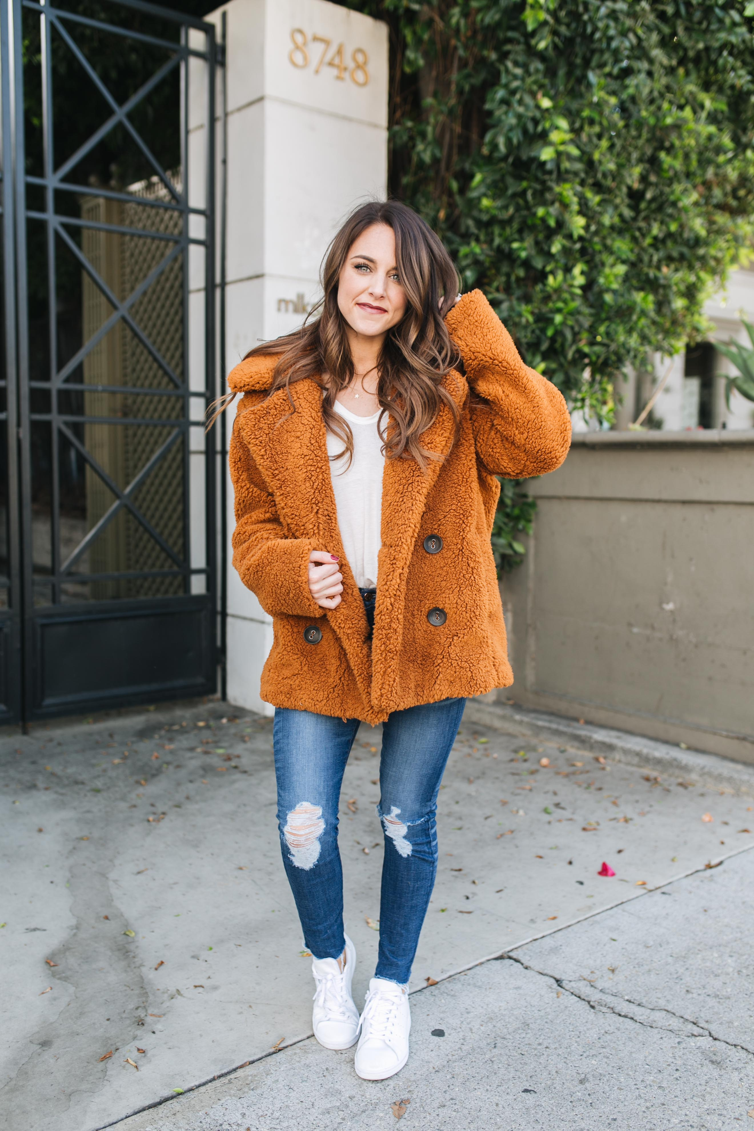 Style blogger Daryl-Ann Denner rounds up top 10 coats under $200 and styles a free people teddy coat and white adidas