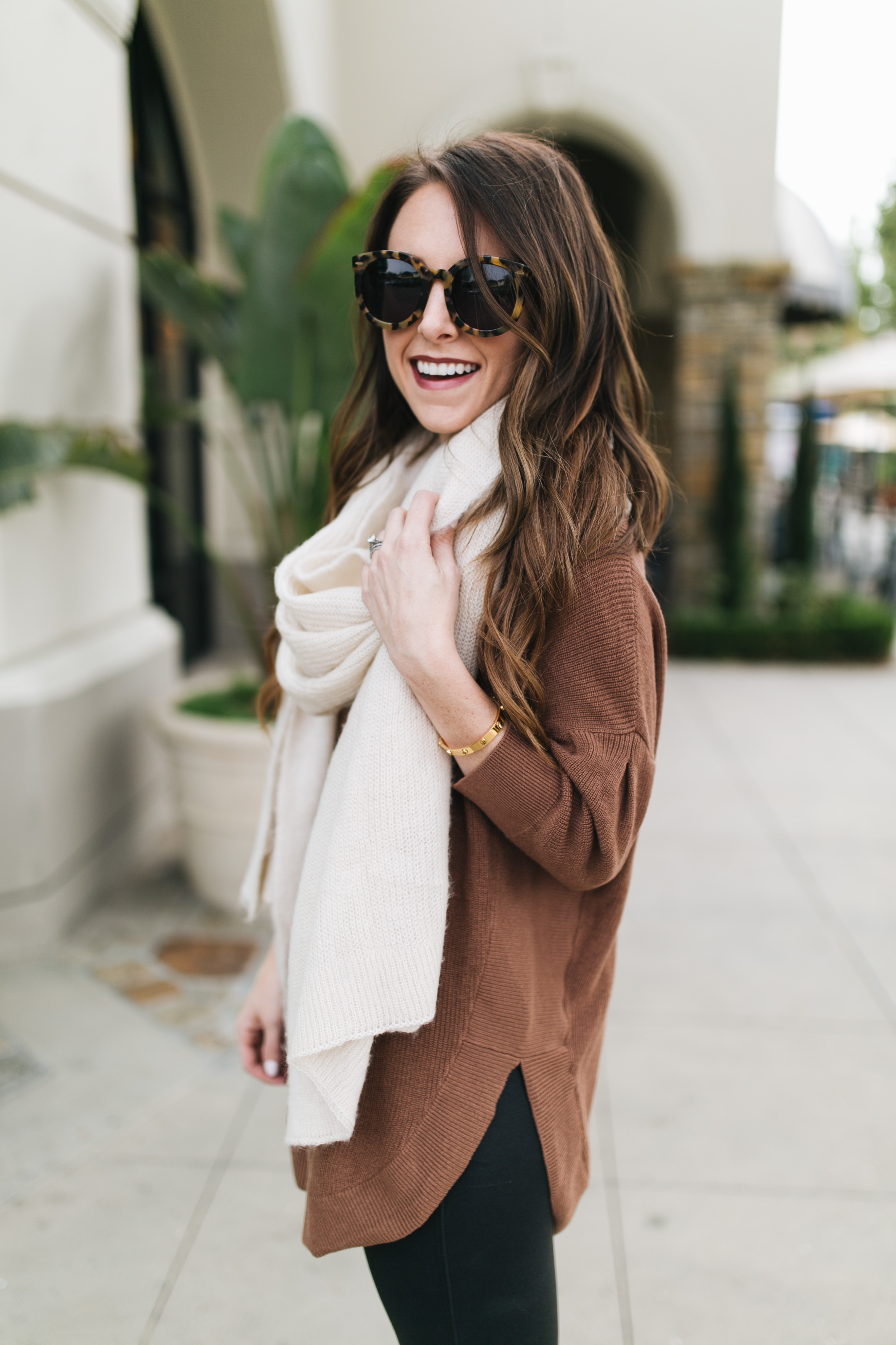 Fashion blogger Daryl-Ann Denner shares the best faux leather leggings under $100 that are super flattering, and styles them with a tunic sweater and scarf and louis vuitton bag