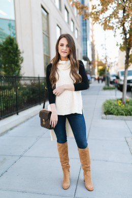 Style blogger Daryl-Ann Denner shares a Free People sleeveless sweater for under $100 and styles it with a black bodysuit and brown suede tall boots