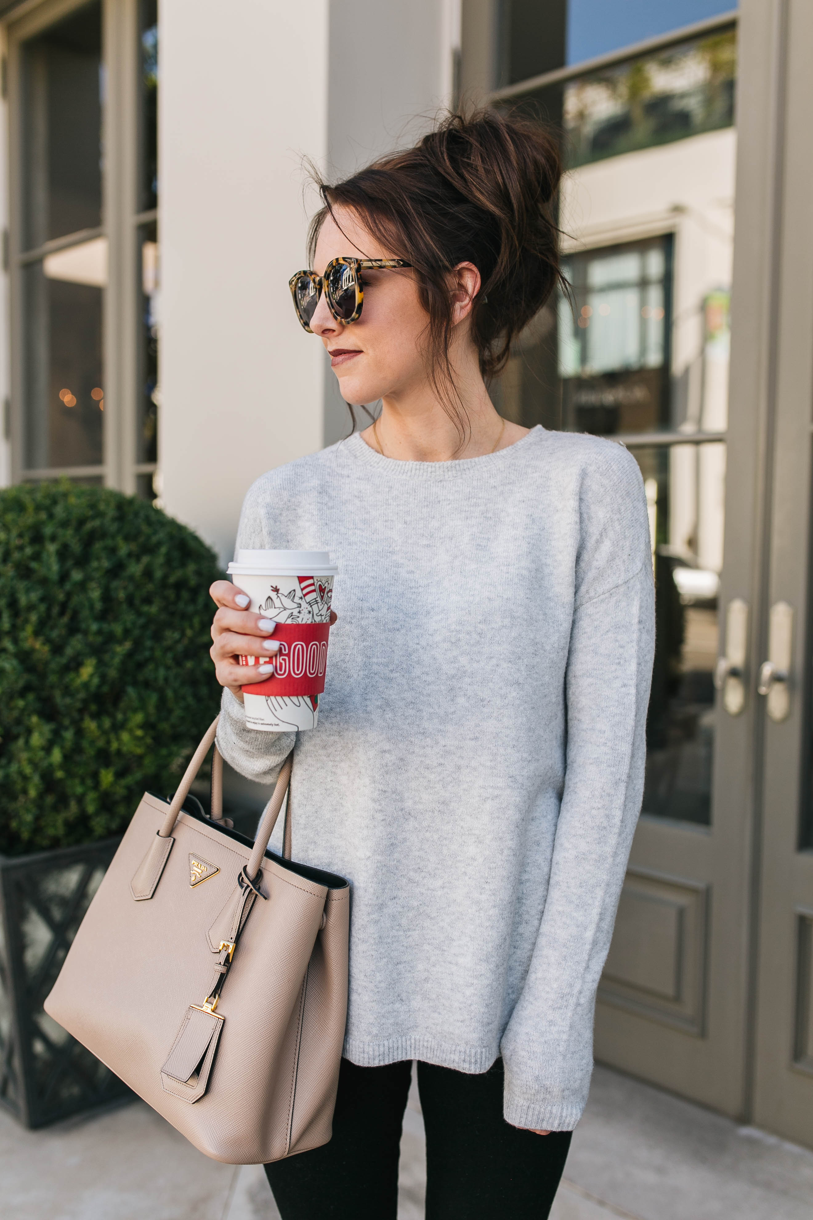 Style blogger Daryl-Ann Denner wears a bow back sweater from Nordstrom, black ripped skinny jeans from Abercrombie & Fitch, a nude Prada bag and a hot chocolate in a Starbucks holiday cup.