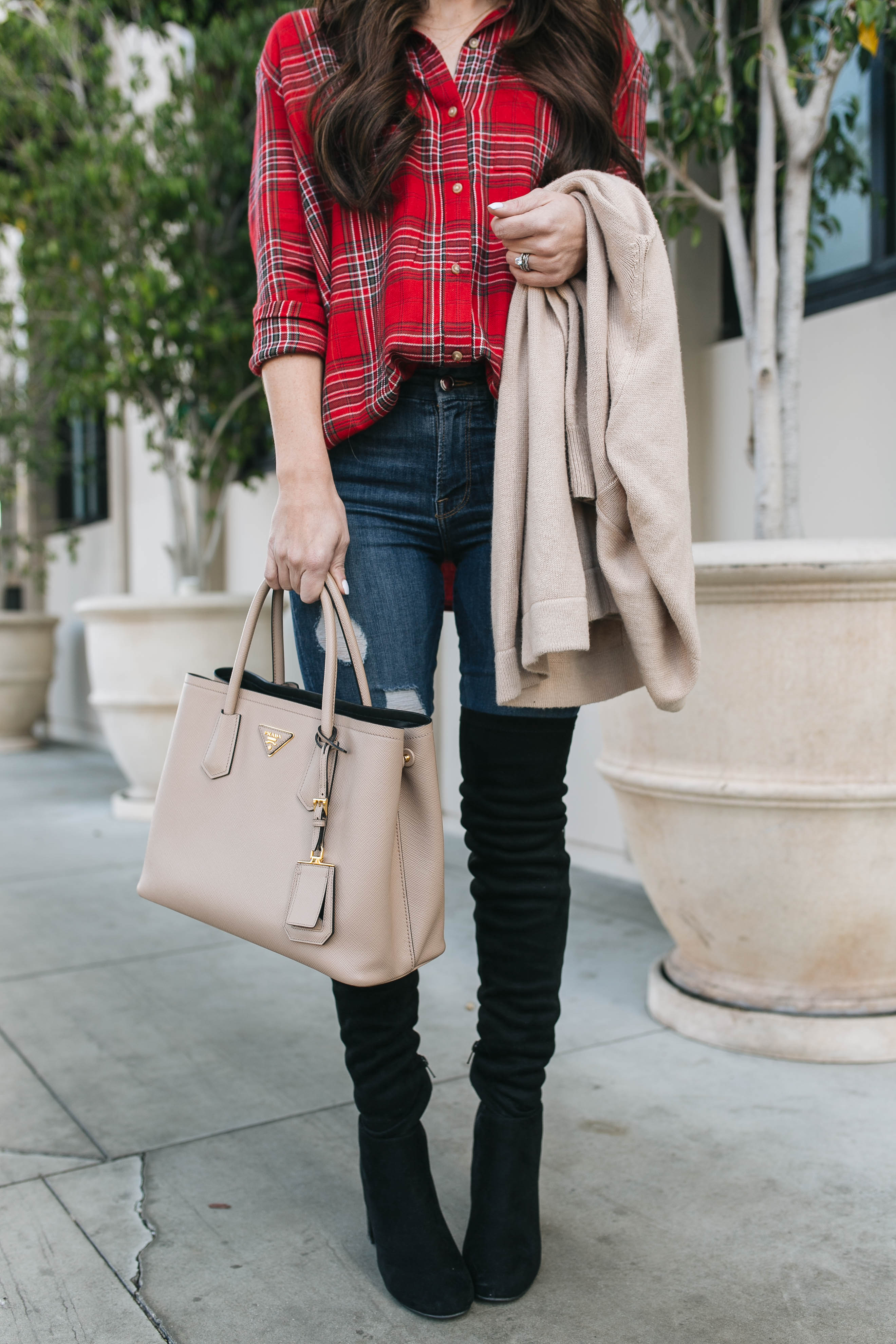 Style blogger Daryl-Ann Denner shares christmas day outfit ideas including red tartan plaid shirt and over the knee boots with good american jeans