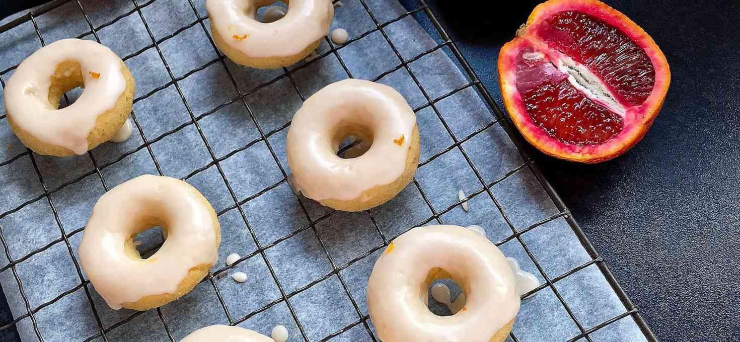 Mini baked vanilla donuts with blood orange glaze