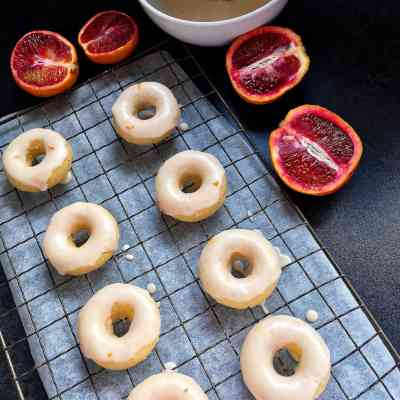 Mini baked vanilla donuts with blood orange glaze