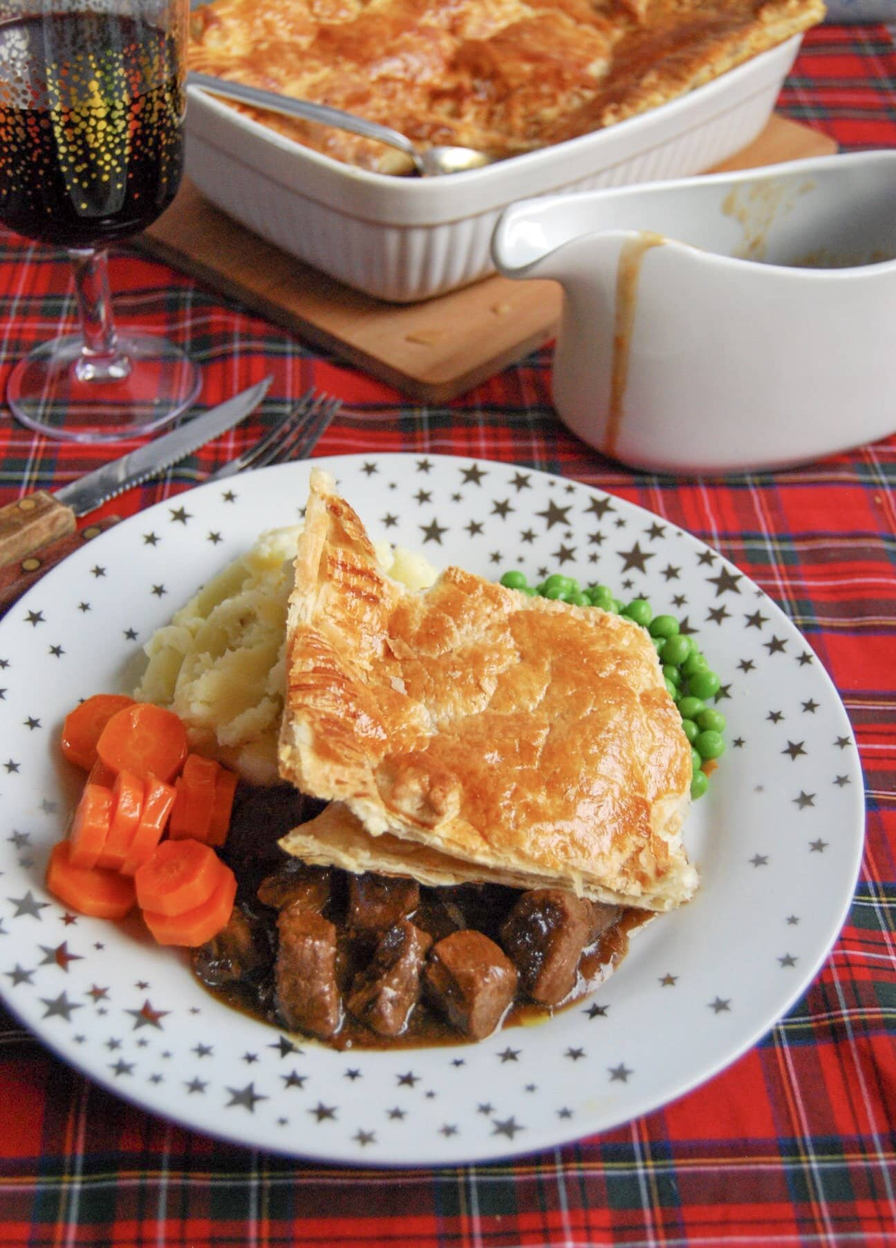 Steak pie with a puff pastry lid and chunks of beef in a rich gravy on a gold and white star place with mashed potatoes, carrots and peas.