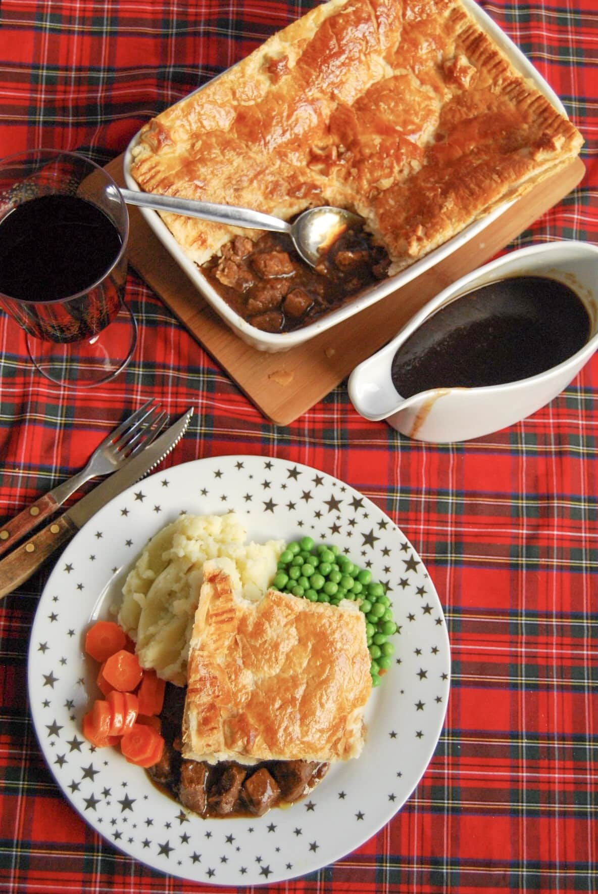 A flatlay photo of a gold and white star plate of steak pie with a puff pastry lid and beef chunks in gravy with mashed potatoes, peas and carrots. A jug of gravy and a large steak pie can also be seen in the top of the photo.