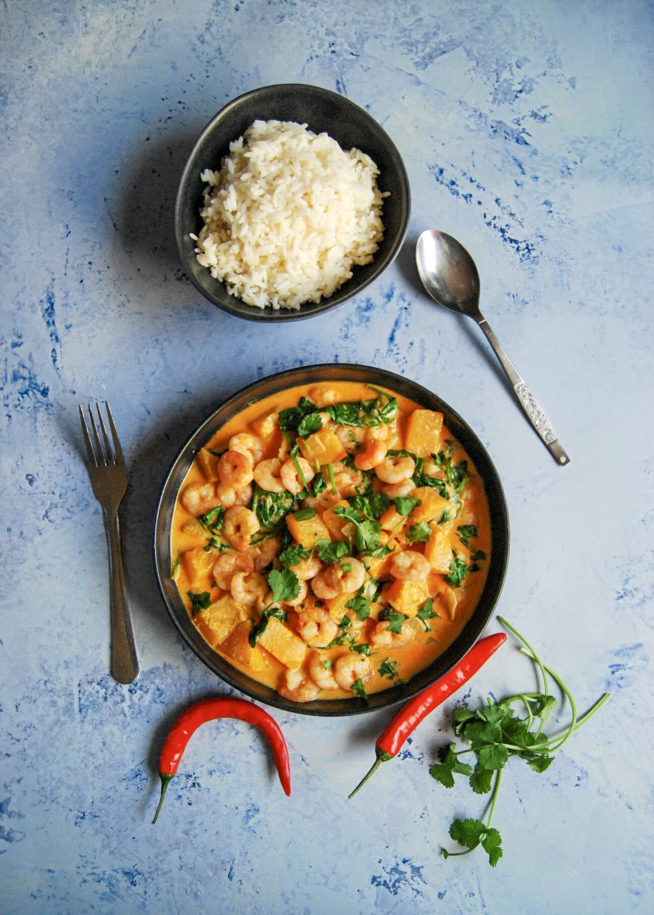 A flay lay photo - blue background with a bowl of prawn red Thai curry sprinkled with fresh chopped coriander.