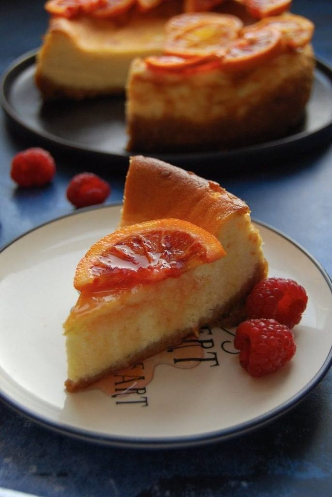 A slice of baked cheesecake decorated with a candied blood orange slice with fresh raspberries on a black and white plate