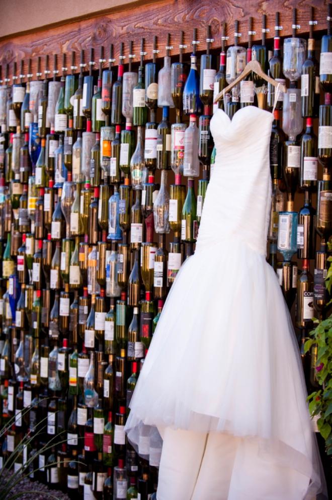 Wedding dress hanging on an amazing wall of bottles