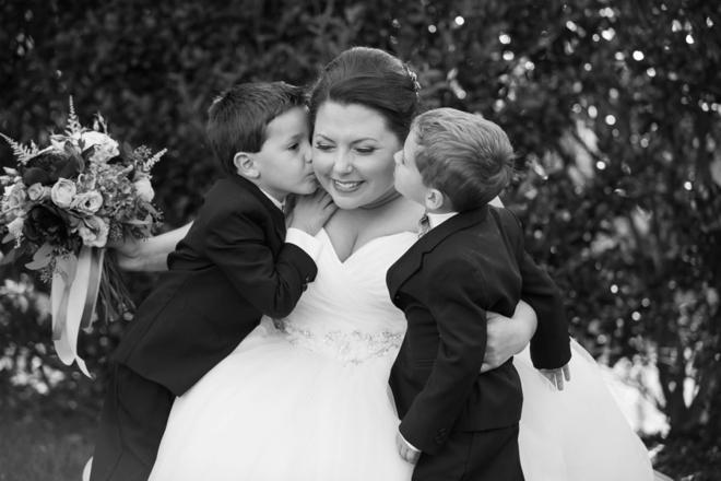 Ring bearers kissing bride