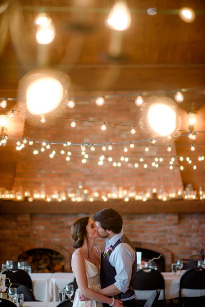 Bride and groom kissing under twinkle lights