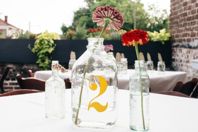Vinyl stickers on vintage glass jars make great DIY table numbers!