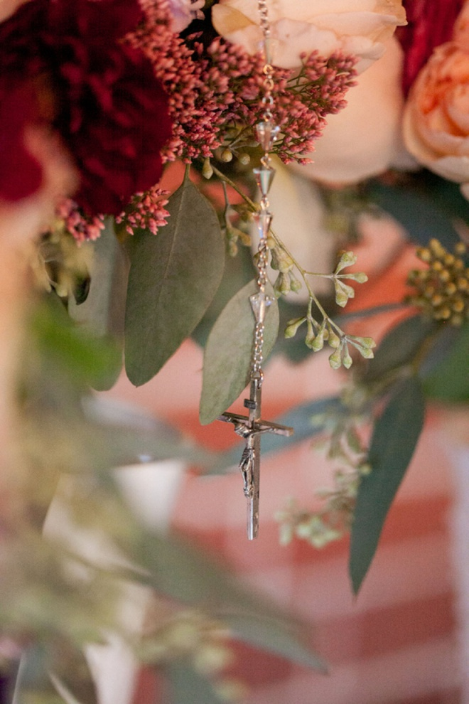 Rosary hanging from the brides bouquet.