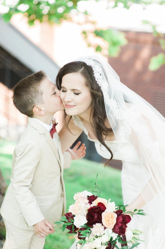 Ring bearer kissing the bride