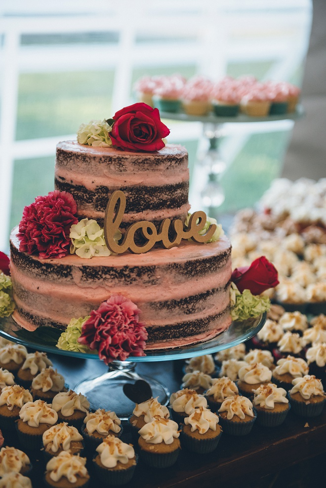 How gorgeous is this wedding cake with gold love cake topper and lots of cupcakes!